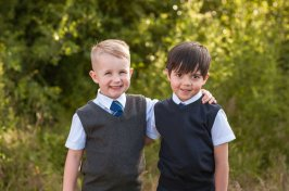 Coloured snap of two little boys in school uniform with the arms wrapped around each other