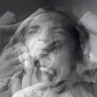 Grey scale photo of person tugging at their hair and mouth open, looks like silent screaming