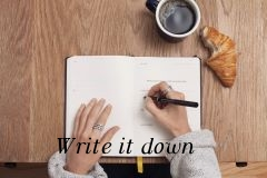 White lady writing in a journal on brown table top with coffee and croissant