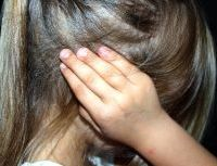 Little girl with ponytail, side view with hand over her ear. Spot the signs of Child Abuse