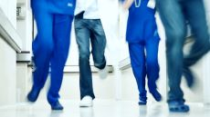 Four doctors dressed in scrubs, running down a corridor