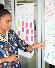 Coloured picture mixed race lady standing by white board covered in post it notes - delivering training