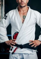 Coloured image of male standing with hands on his hips, wearing a karate black belt