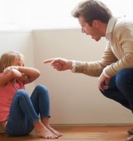 Coloured image of a little girl on floor with elbows on her knees. Man kneeling down, pointing at her and shouting