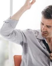 coloured image man looking at sweat on his shirt under his arm