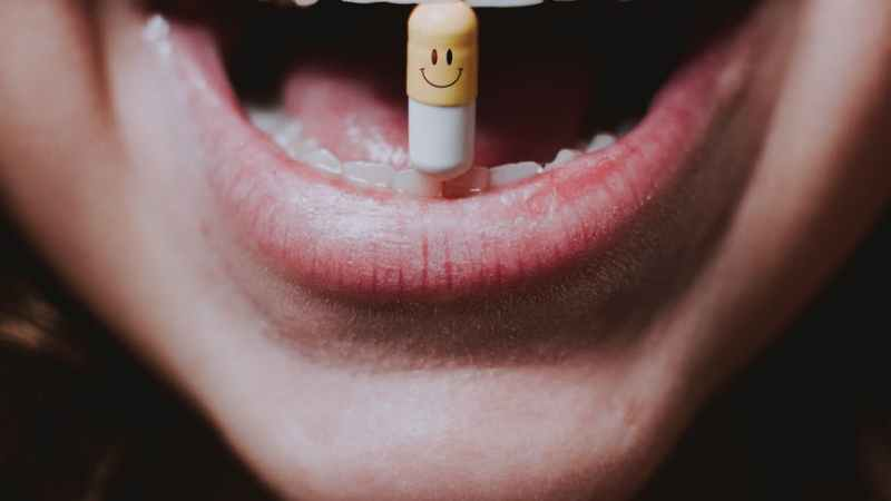 faceless woman with pill in teeth and nose piercing