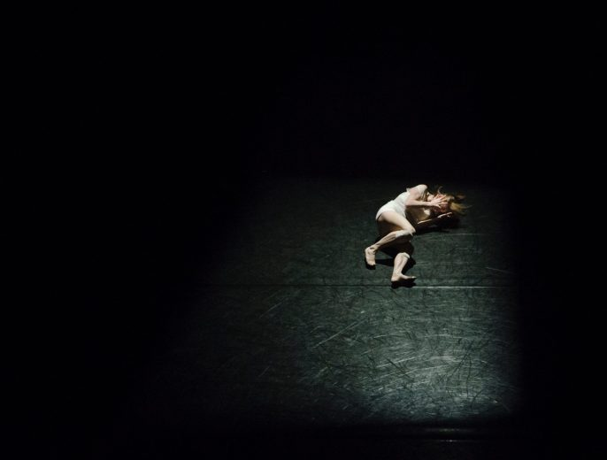 Frightened woman lying on the floor in a dark room