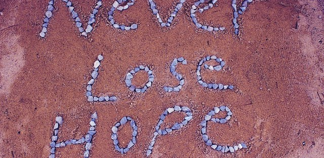 """""""Never lose hope"""" spelled out with pebbles on the ground"""
