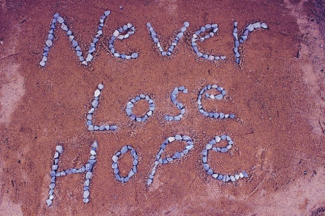 """Never lose hope"" spelled out with pebbles on the ground"