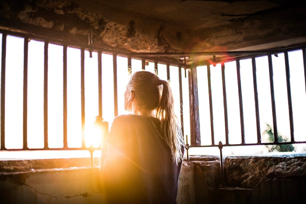 woman looking out from a cell with barred windows