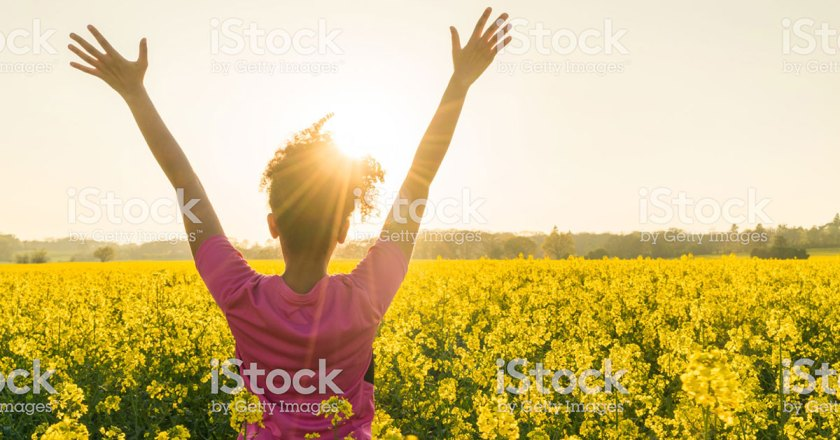 woman with hands raised in canola field