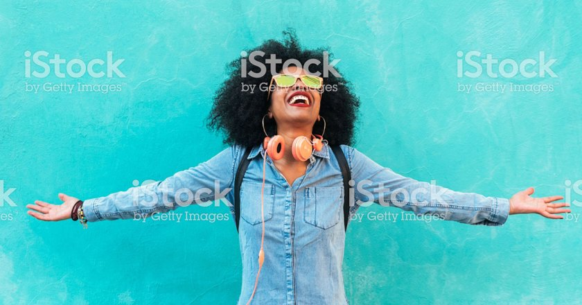 woman smiling and looking up with arms spread