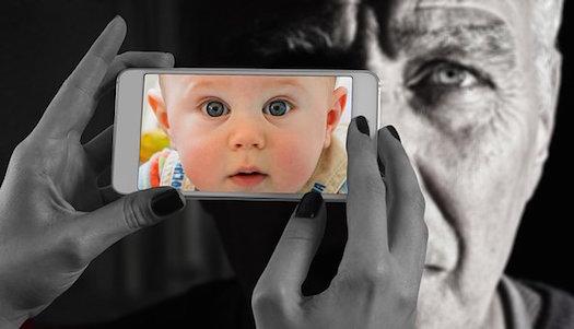 老人とスマホに映る赤ちゃん