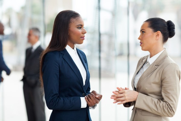 two women with serious expressions having a conversation.