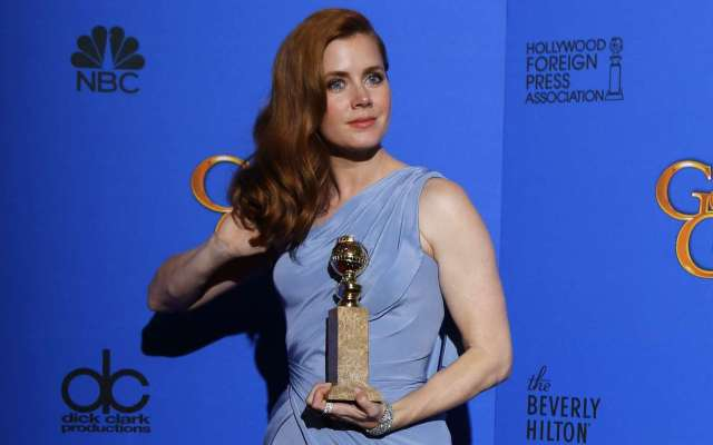 "Amy Adams poses with her award for Best Actress In A Motion Picture, Musical or Comedy for her role in ""Big Eyes"" backstage at the 72nd Golden Globe Awards in Beverly Hills"