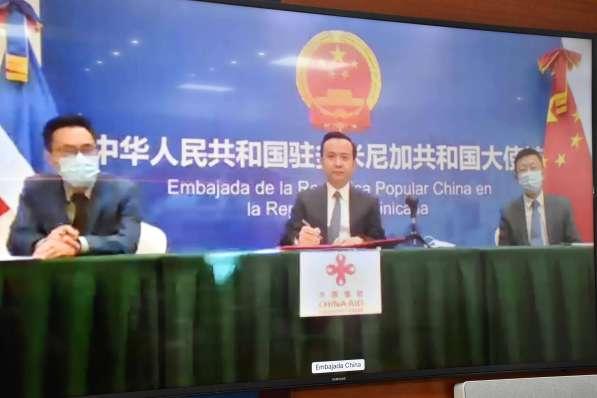 El ministro de Economía, Planificación y Desarrollo, Miguel Ceara Hatton, y el embajador de la República Popular China en el país, Zhang Run firman el acta de entrega de donación de material antiepidémico. Cada uno en sus sedes ministeriales y diplomáticas.