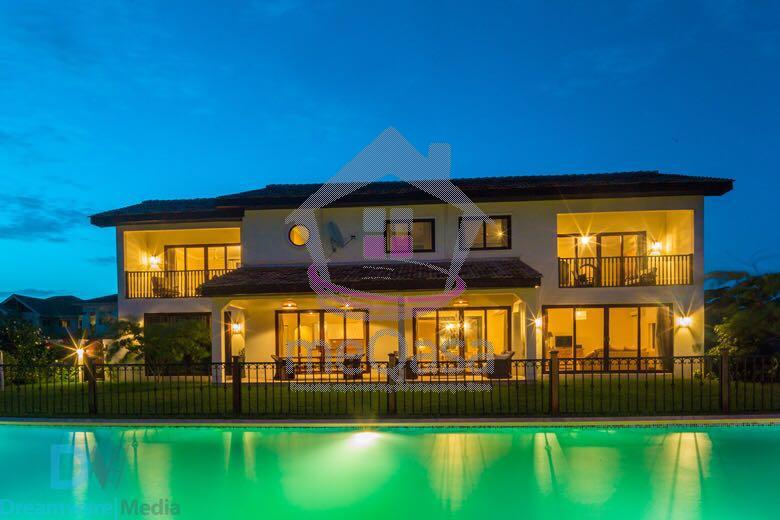 Evening shot of one of the expensive Accra properties at Airport Hills featuring a sparkling pool and beautifully lit rooms.