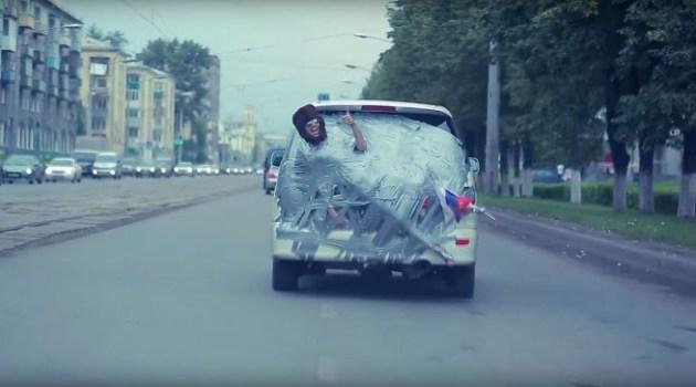 Russos colam seu amigo na traseira do carro e vão passear pela cidade