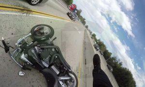 Motociclista bate e fica em cima de carro em movimento
