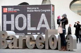 A woman takes pictures in front of the Mobile World Congress in Barcelona on February 24, 2013, a day before the start of the 2013 Mobile World Congress. The 2013 Mobile World Congress, the world's biggest mobile fair, is held from February 25 to February 28 in Barcelona.  AFP PHOTO / LLUIS GENE