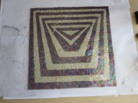 mosaic with tape over the top getting ready to be lifted into the tray