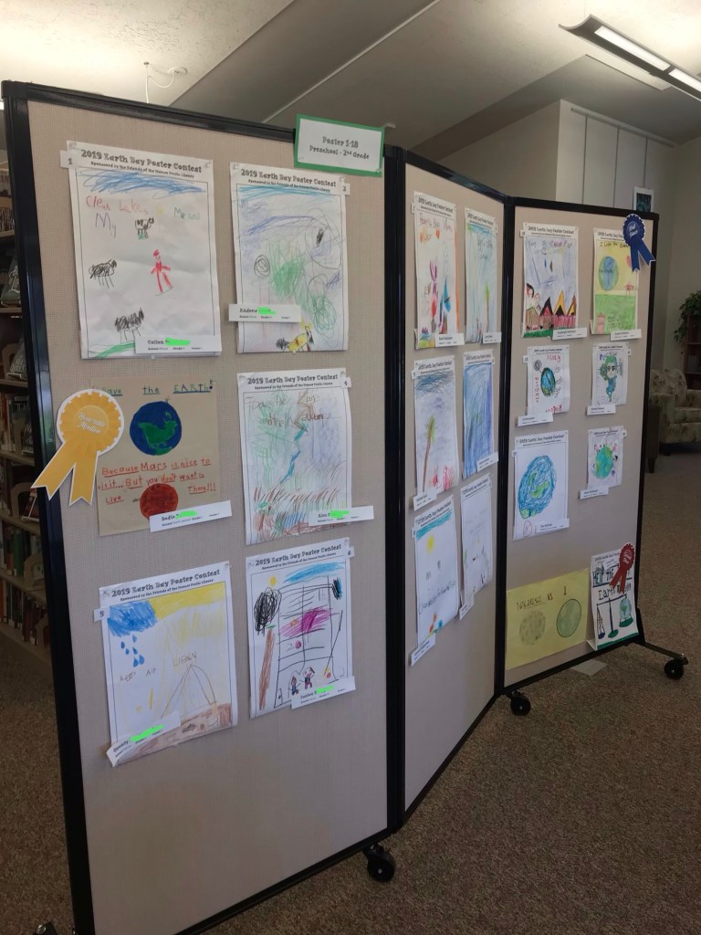 Earth Day poster entries displayed on a movable wall in the library