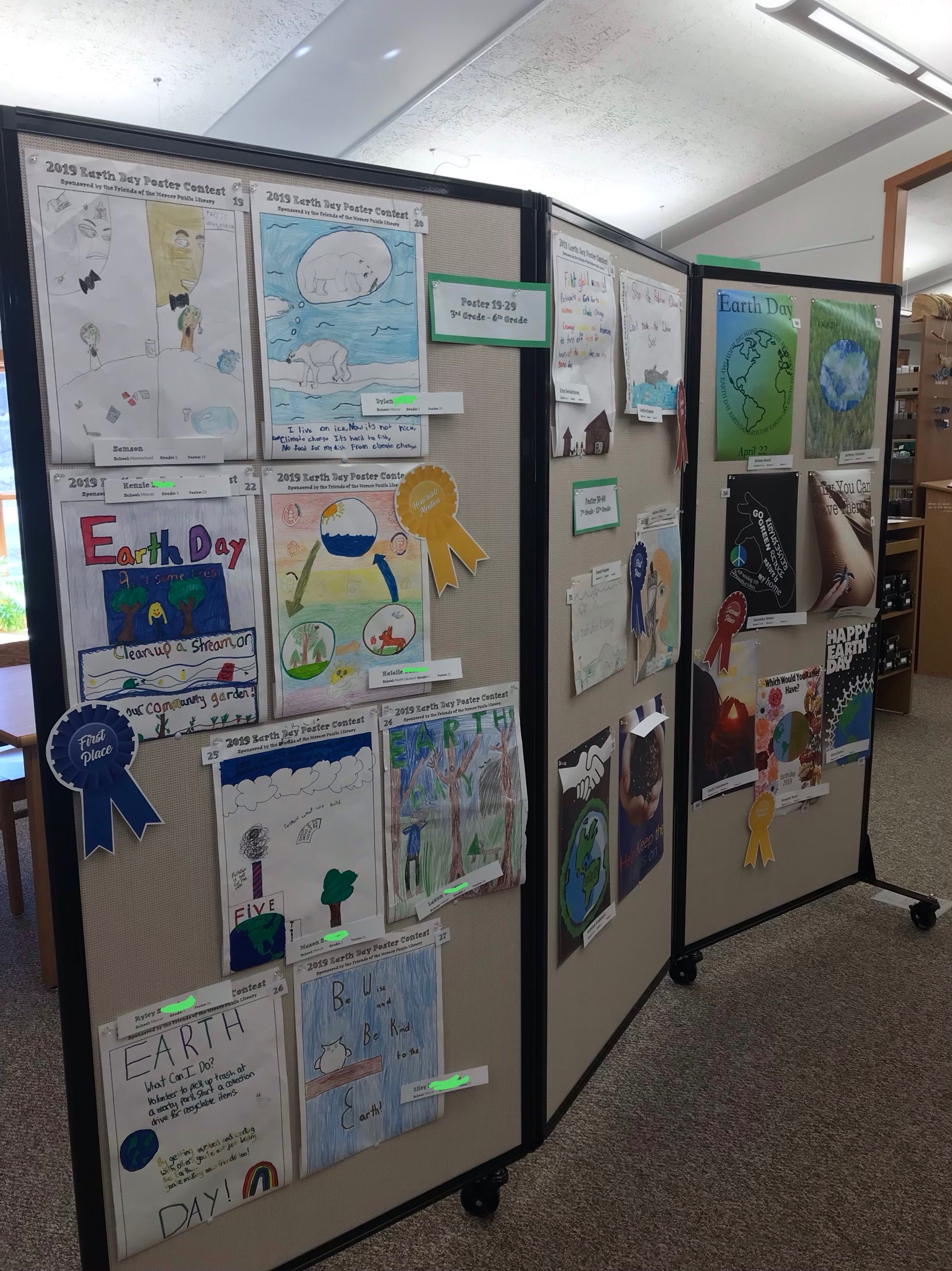 Earth Day poster contest entries displayed on a movable board in the library