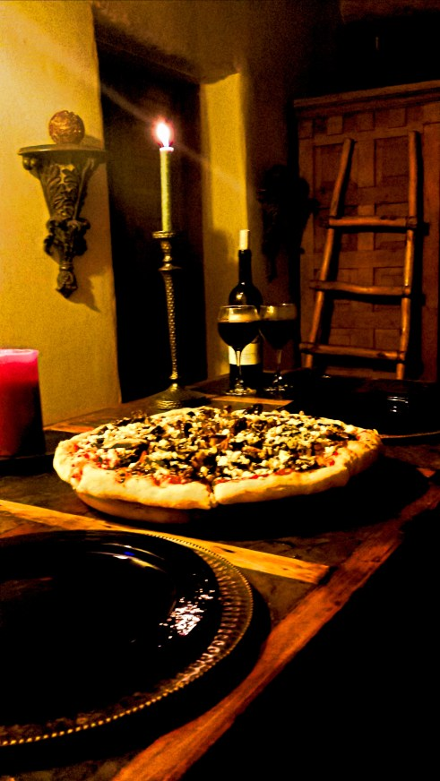 A dinner view of pizza accompanied by none other than a fabulous chianti