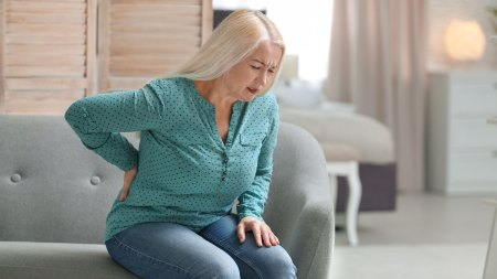 Woman suffering from acute back pain on couch