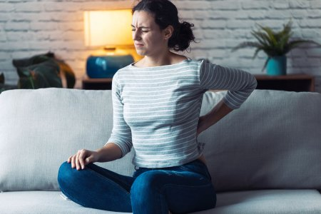 young woman sitting on couch experiencing back pain