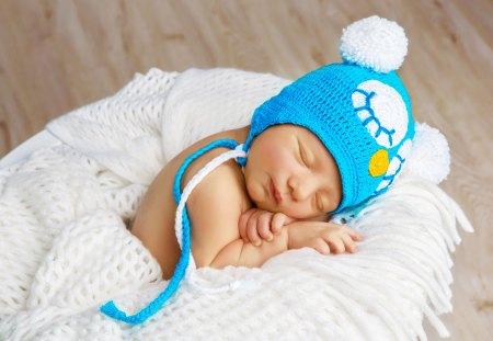 newborn baby sleeping in blue hat