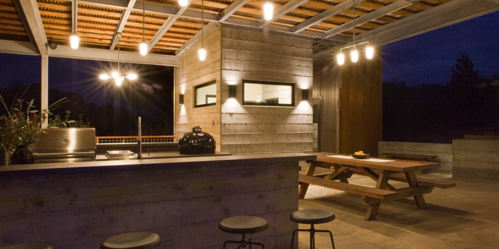 nighttime image of modern outdoor kitchen with dining table