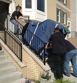 Rob, Austin and Greg safely bring a 650 pound grand piano down 11 steps.