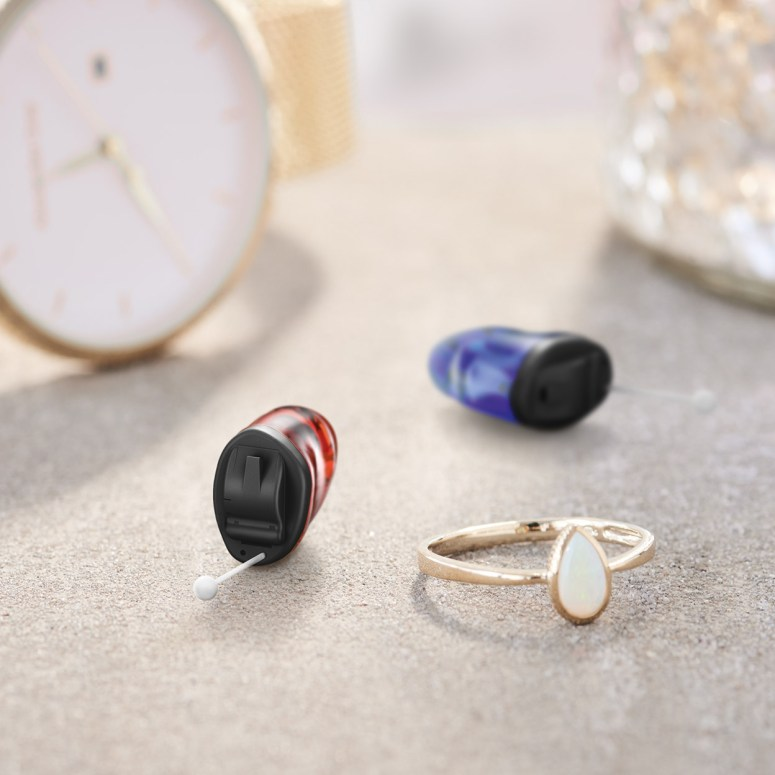 Pair of Signia Insio Custom NX hearing aids shown with a ring in the foreground and a watch in the background