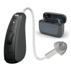 Black ReSound Linx Quattro hearing aid in foreground. Black hearing aid charger shown in background