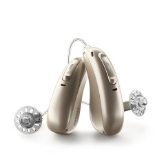 Pair of champagne Phonak Audeo Paradise hearing aids standing up