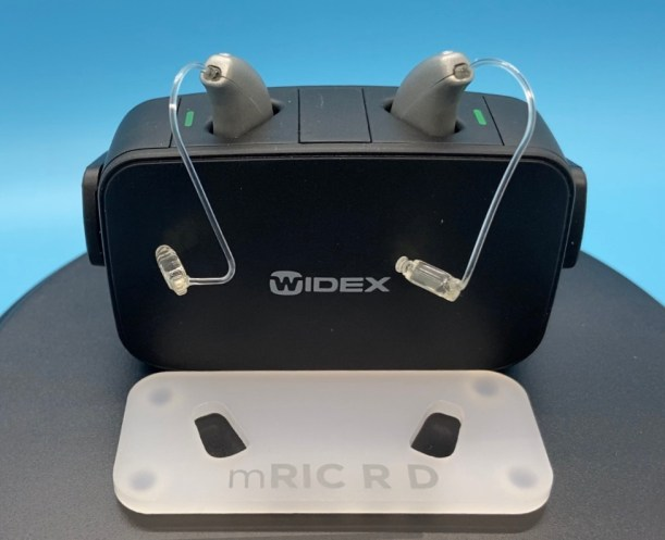 Pair of Widex Moment hearing aids inside charging case