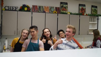 two teenage girls and three teenage boys smiling in kitchen with thumbs up
