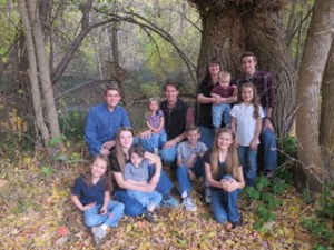 Mom and Dad with nine kids in front of tree