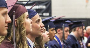 boys and girls sitting in graduation ceremony in blue and burgundy robes