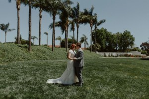 married couple kissing in front of palm trees