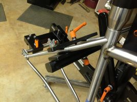 using the clamping plates of the fixture's tube holder