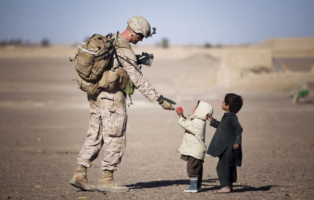 Be kind soldier military uniform american accepting a flower from a child