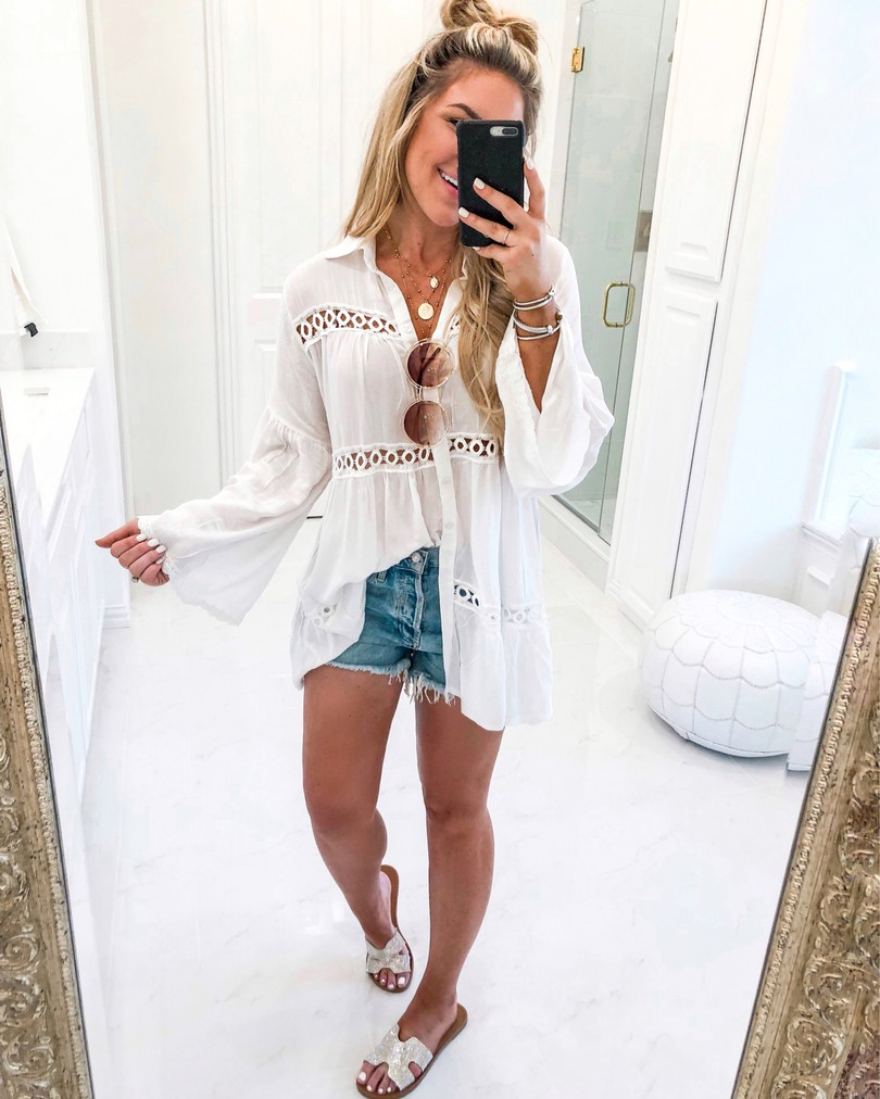 girl in white cover up taking mirror selfie