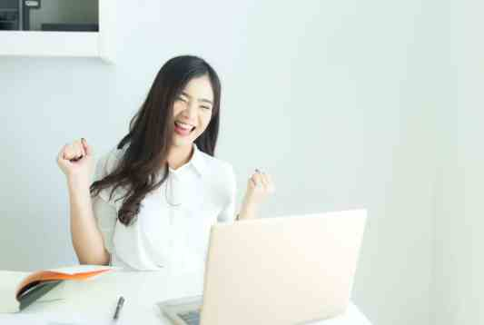 Happy young asian business woman finished her work at workplace