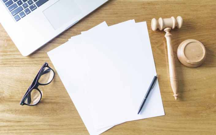 High-angle-view-of-blank-papers-laptop-gavel-spectacles-and-pen-on-wooden-background
