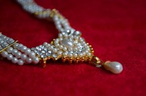 diamond and pearl necklace on a red velvet surface