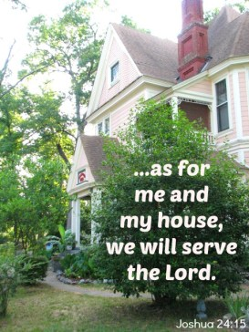 Scripture--Joshua 24:15 written on a bushy tree in front of an old, restored house