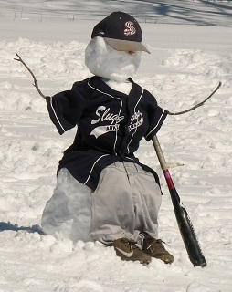 a small snowman dressed in a baseball uniform complete with bat and shoes