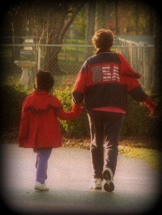 grandmother and child walking in the park in their coats on a cool day